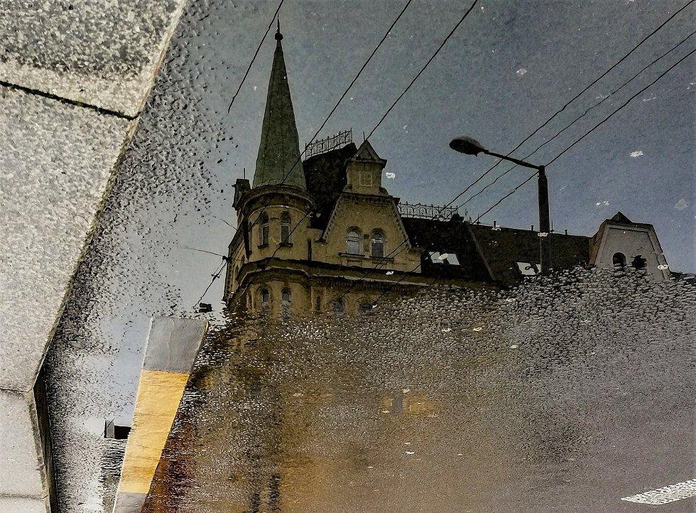 Ústecký fotograf Martin Vodňanský si oblíbil snímky zachycující dominanty města nad Labem v odrazu kaluže. Říká jim loužovky. Na snímku je na budovu Komerční banky.