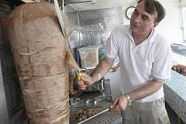 Prodavač porcuje kebab. Podobný si před nedávnem z  pojízdné prodejny u Tesca (na snímku dole)  odnesli zloději. Spolumajitelka rychlého občerstvení nechápe, že si někdo kradené maso koupí.