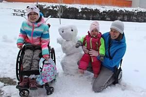 Sestry Saša a Máša z Dobětic se svou maminkou využily sněhové nadílky u školy starší z dívek a pustily se nadšeně do stavby sněhuláka.