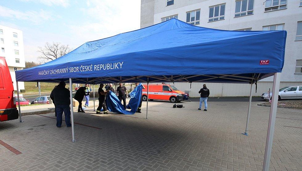V Ústí nad Labem v Masarykové nemocnici dnes stavěli hasiči třídící stan (červený) a odběrové místo (modrý stan).