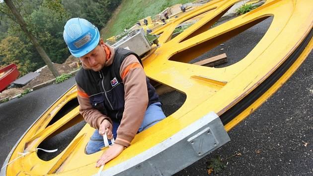 Technici připravují kusy lanovky k montáži. Velké ocelové části lanovky včetně pohonných kol a vysokých stožárů jsou rozložené na parkovišti v lyžařském středisku Telnice.