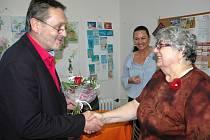 Náměstek Jiří Madar předává květinu vedoucí klubu Elixír na Bukově Květoslavě Votrubcové.