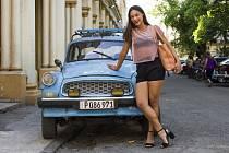 Náhodně kolemjdoucí kubánská slečna se na přání fotografa opřela o starou Škodou Octavia v ulicích Havany.
