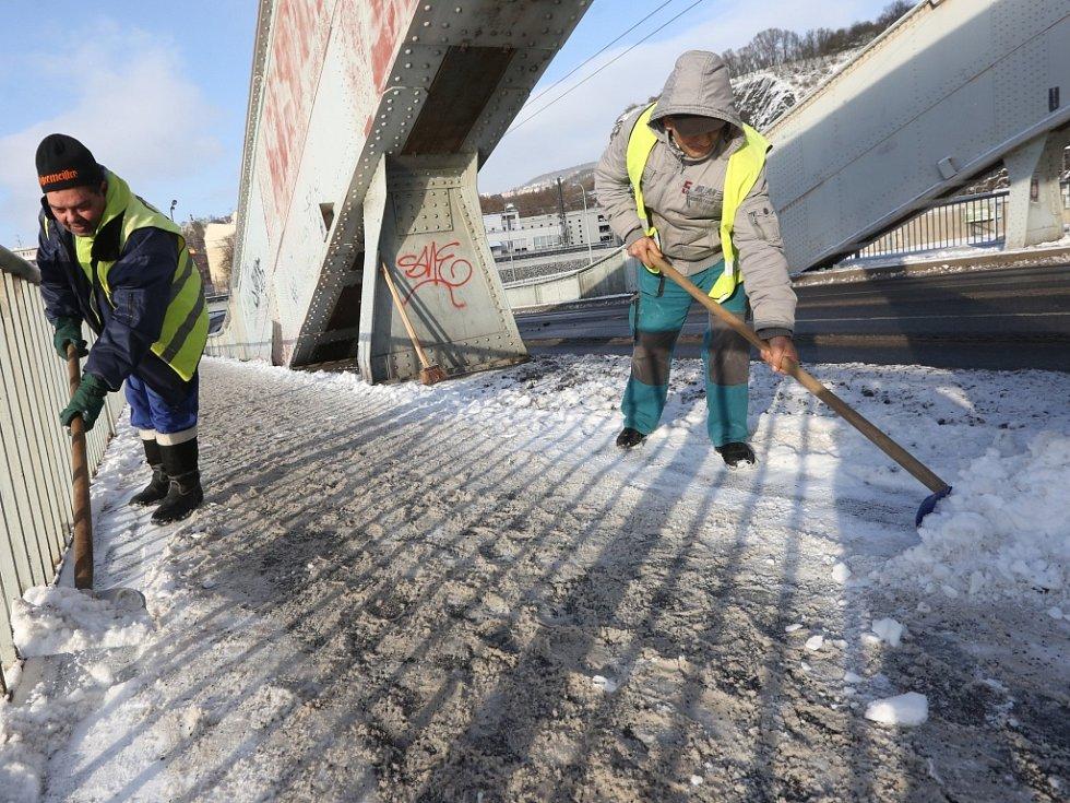 Veřejně prospěšní pracovníci střekovského obvodu Tichomir Cicu a Andrej Rejdaj odklízeli sníh na Benešově mostě.