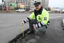 Dopravní policista ukazuje hloubku výmolu na Severní Terase