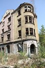 Pohled na ulici Na nivách se zdevastovanými domy, které hrozí zřícením.