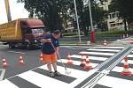 Pracovníci firmy Dopravní značení Kolos, obnovují značení přechodů pro chodce na ulici Sociální péče.