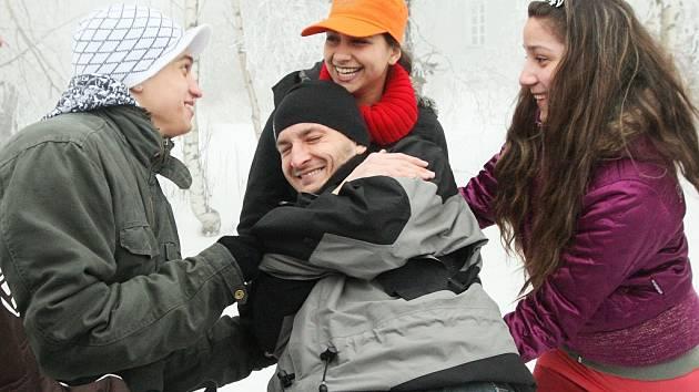Romští školáci z Trmic hrají na sněhu  s učitelem z Pedagogické fakulty Univerzity J. E. Purkyně Janem Wedlichem (uprostřed) hru, která je naučí věřit druhým  i sobě.