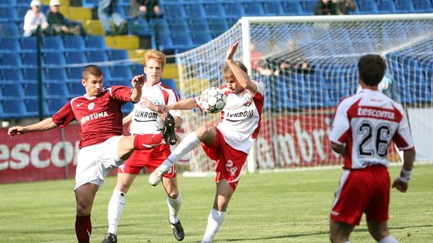 ŠAVLOVÝ TANEC. Zlínský obránce Vlastimil Vidlička (vpravo) bojuje o míč s útočníkem Sparty Janem Rezkem. Vše sleduje Tomáš Janíček.