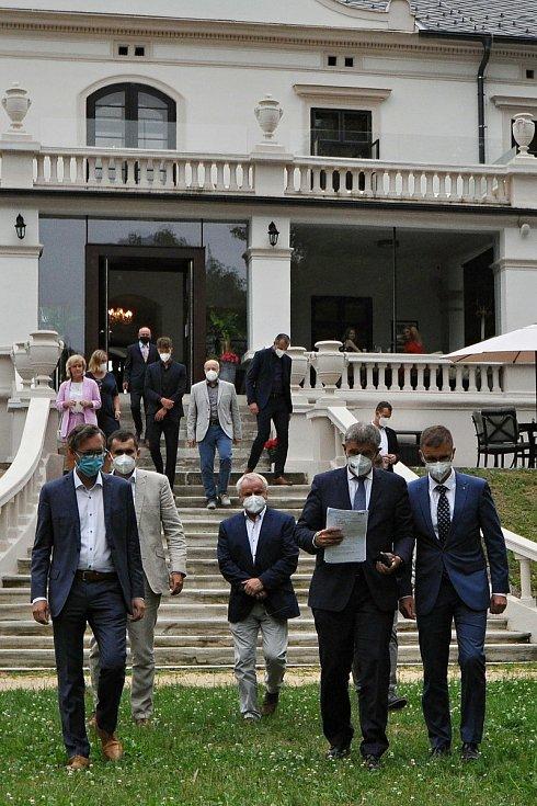 Premiér Andrej Babiš (druhý zprava) přichází ve středu 14. července 2021 v doprovodu hejtmana Zlínského kraje Radima Holiše (vpravo) na setkání s novináři do parku u zámku Wichterle ve Slavičíně.
