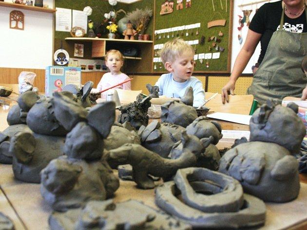 Děti vytvářejí v keramickém kroužku roztodivné figurky.