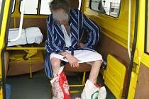 Muž v županu s igelitovými taškami na nohou.