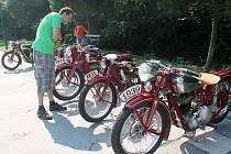 Návštěvník sjezdu motorek obdivuje historické stroje značky Jawa