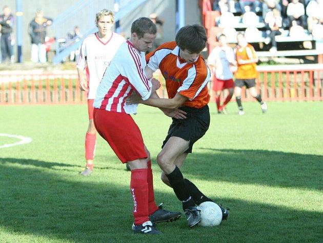 V zápase mezi Viktorií Otrokovice B (v bílém) a Ořechovem o něj bojují dva fotbalisté.