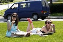 Studenti odpočívají přes poledne na trávníku Gahurova prospektu ve Zlíně.