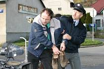 UŽ HO VEDOU. Polapeného lupiče bot Gustava Řezníčka odvádí před bedlivým okem kamery policista. Toho si včera v Loukách zahrál Radoslav Šopík