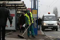 Pracovník Zlínských technických služeb odstraňuje posypový materiál na zastávce MHD.