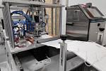 Budoucí respirátor opatřený gumičkami dále putuje ke svařovacím přístrojům