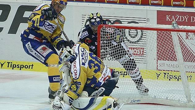 Hokej Zlín (ve žlutém) - Liberec. Obránce Linhart s gólmanem Sedláčkem odolávají náporu soupeře