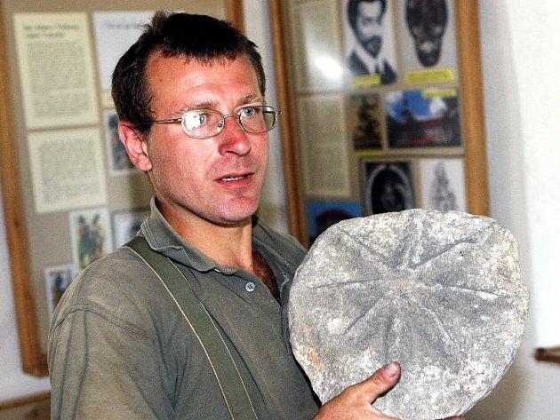 Kastelán David Juříček drží v rukou jeden z nejvzácnějších letošních archeologických nálezů na lukovském hradu, kamenný erb s osmicípou hvězdou rodu Šternberků.