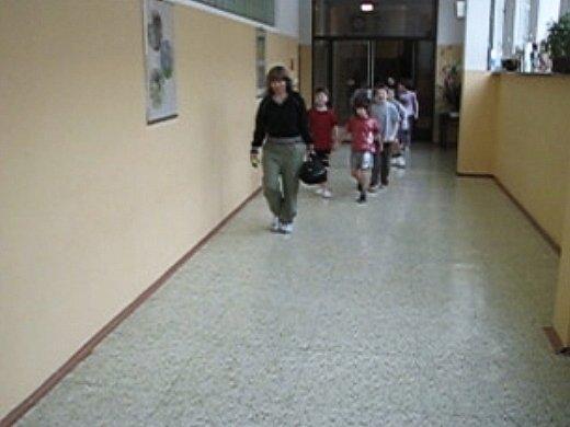 Po chodbě přicházejí děti s učitelkou. Nad tím, že proti ní jde cizí člověk, se nepozastaví.
