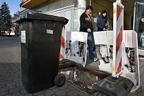 Díru po propadlém poklopu chrání popelnice.