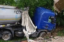 Tahač se převrátil i s přívěsem a zatarasil vozovku po celé šířce. Povrch silnice pokryla vrstva vysypaného makadamu a z poškozené nádrže tahače začala unikat nafta.