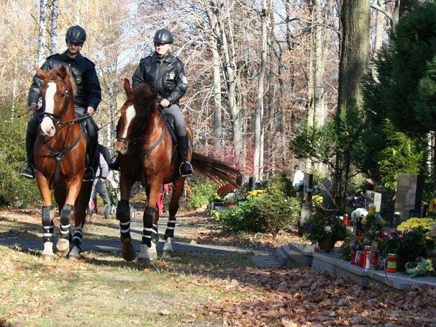 Hřbitov hlídají policisté na koních.