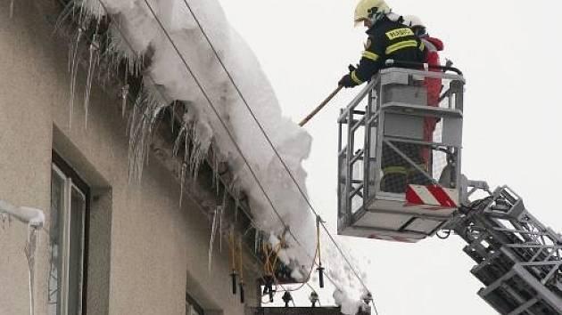 Hasiči odstraňují sníh a rampouchy ze střech.