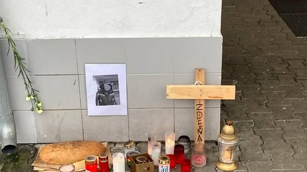 Na místě, kde muž bez domova sedával, hoří zapálené svíčky