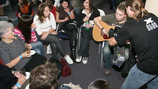 Zpěvák Standa se snažil zkrátit dlouhou chvíli hrou na kytaru. Měl úspěch, spousta lidí se k němu připojila.