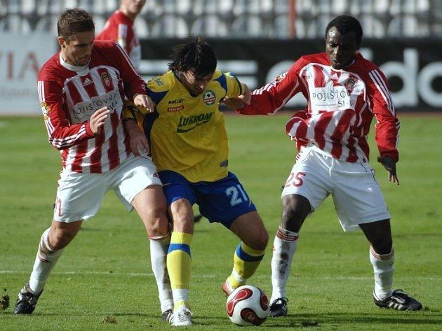Zlínský záložník David Šmahaj (ve žlutém dresu) se snaží uniknout dvěma fotbalistům Žižkova