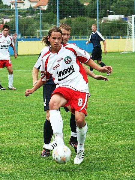 Útočník zlínské devatenáctky Štěpán Červenka (v bílém) si chrání míč před obráncem Slovácka Markem Bučákem.