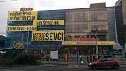 BERANI, DO TOHO! Budova prodejny Baťa ve Zlíně v Dlouhé ulici se oblékla do modré plachty, na které žlutě září například nápis Dej, ševče, gól!