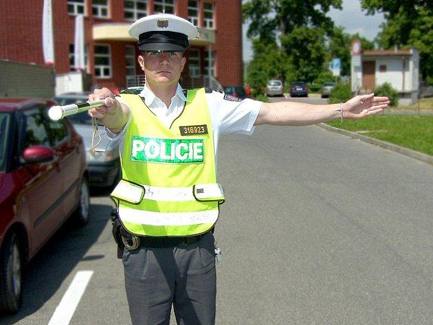 Policista řídí dopravu, jeho gesto: Stůj! pro řidiče za jeho zády, Volno. pro odbočující doprava.