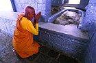 Poutník se modlí uotisku chodidla veskále.