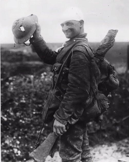 Voják, který ukazuje helmu, která mu zachránila život.