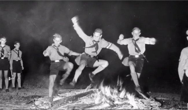 Kluci skákající přes oheň.