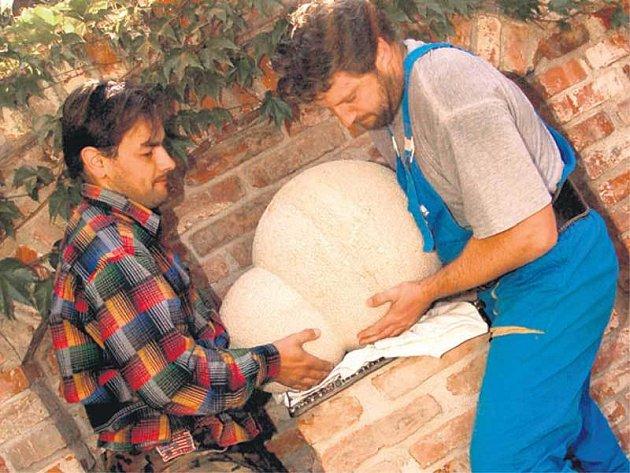 Kameník Tomáš Wech (vpravo) instaluje s pomocníkem obří pískovcovou kvasinku.