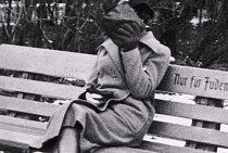 """Židovská žena, která si halí tvář, aby nebyla poznat. Na lavičce je nápis """"Pouze pro Židy"""". V roce 1938, z kterého je fotka, byli Židé striktně separováni od nežidovského obyvatelstva."""