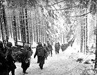 Američtí vojáci pochodující lesem