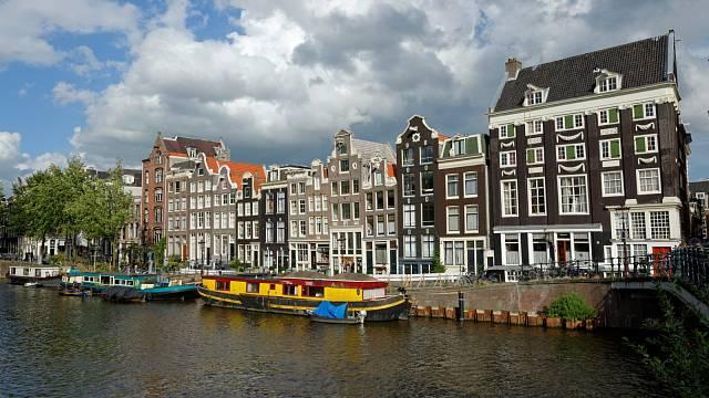 Úzké domky s nesouměrnými okny lemované vodními kanály. Tak vypadá historické centrum Amsterdamu.