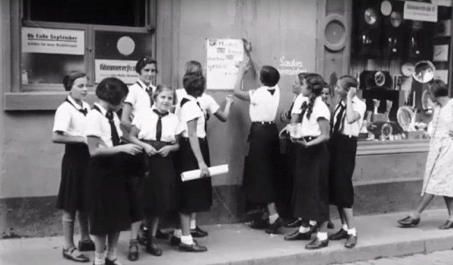 Děvčata věší rekrutující plakát.