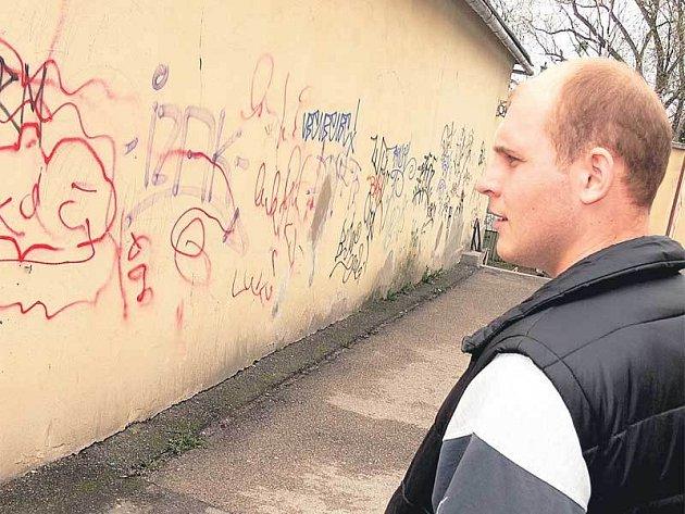 Tomáš Hejda kontroluje sprejerské nápisy na farní zdi.