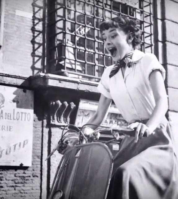 Audrey Hepburn při projížďce městem na Vespě.
