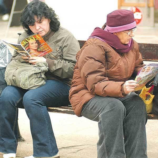 Čekání na vlak si lidé krátí třeba četbou tisku.