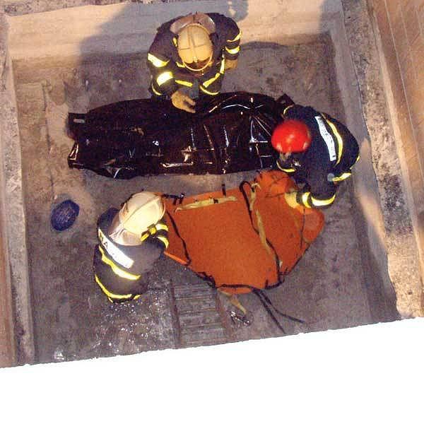 Zaměstnanec bezpečnostní služby pád do hluboké šachty nepřežil. Nahoru jeho mrtvé tělo vytahovali hasiči pomocí trojnožky.