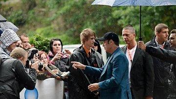 Travolta jde na sobotní tiskovou konferenci. V modrém saku a legrační bejzbolce.