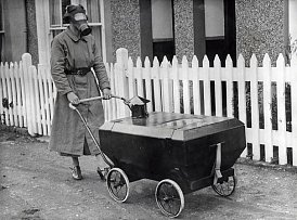 Maminka s plynovou maskou a děťátko v plynovém kočárku na procházce. Londýn, 1938.