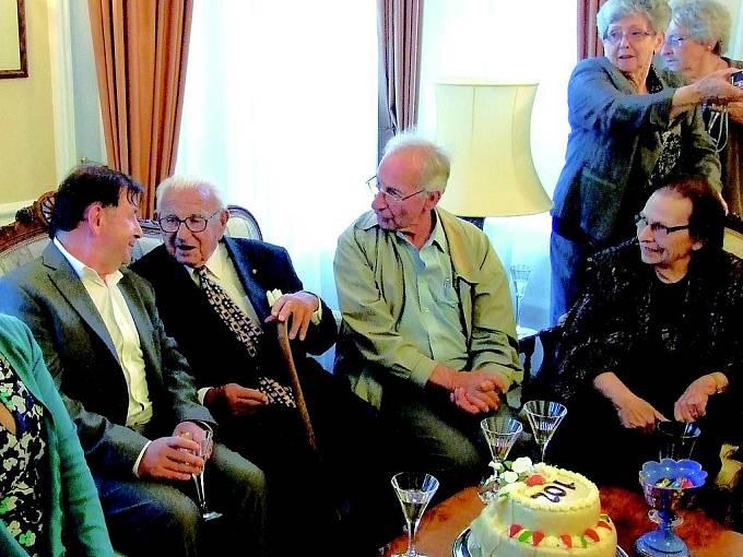 Oslava 102. narozenin sira Nicholase (uprostřed s hůlkou) v Londýně letos 19. května. Vlevo od oslavence je český velvyslanec Michael Žantovský, zcela vpravo sedí Dagmar Šímová.